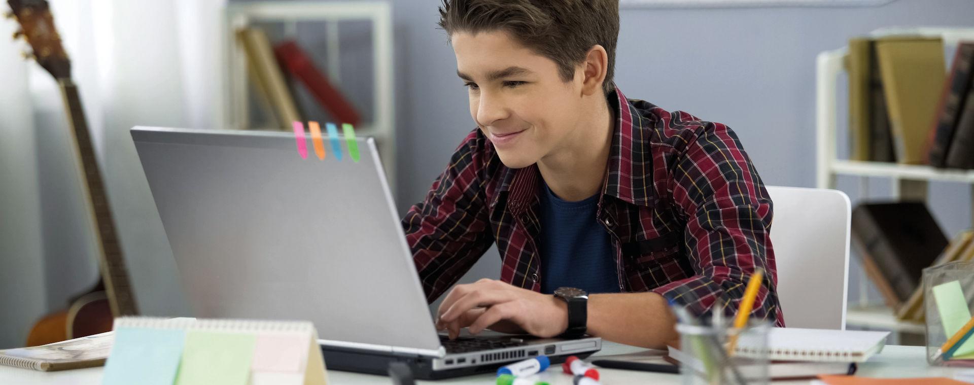 Schüler vor Laptop bei Hausaufgaben Foto: motortion - Adobe Stock